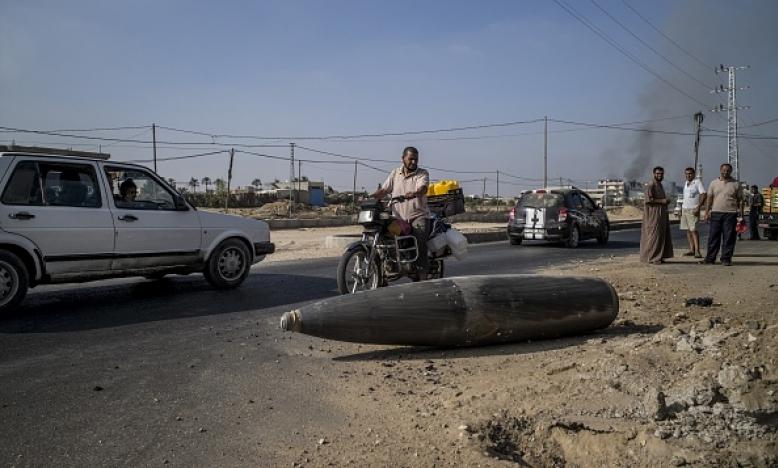 Op 1 augustus 2014 rijden Palestijnse automobilisten langs een externe brandstoftank van een Israëlische straaljager in Deir al-Balah, in de centrale Gazastrook