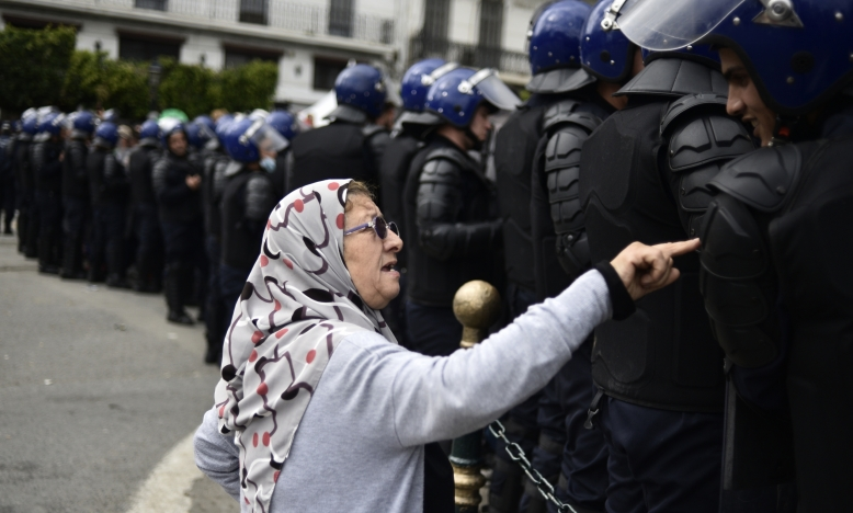 Een oudere Algerijnse vrouw praat met een lid van de veiligheidstroepen die een protestgebied afzetten tijdens een anti-establishment demonstratie in de hoofdstad Algiers, op 10 april 2019. © Ryad Kramdi / AFP via Getty Images