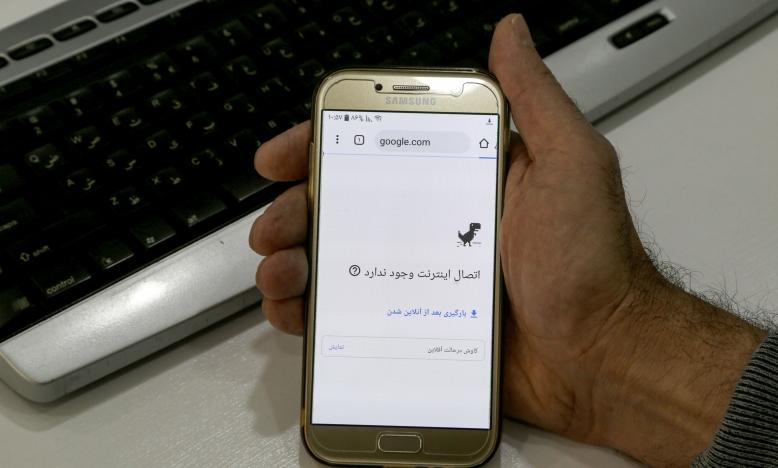 Een man houdt een smartphone vast, verbonden aan een wifi netwerk zonder internettoegang in een kantoor in de Iraanse hoofdstad Teheran, op 17 November 2019. De autoriteiten implementeerden een bijna volledige shutdown van het internet sinds de massademonstraties die twee dagen eerder uitbraken. © Atta Kenare/AFP via Getty Images