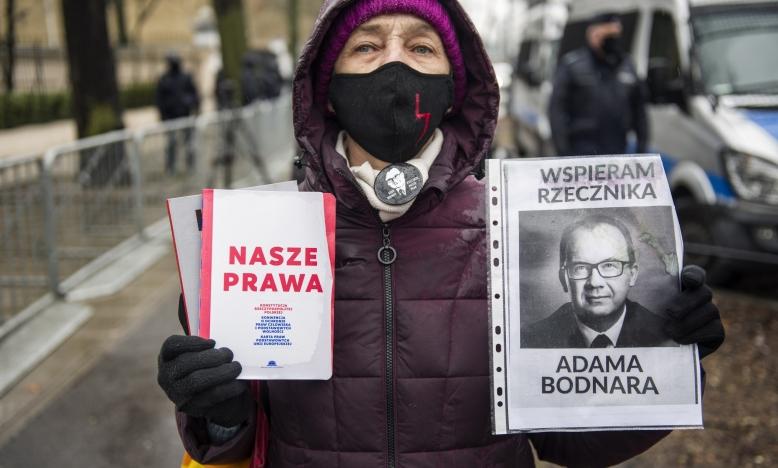 Supporter van Pools ombudsman Adam Bodnar staat buiten aan het Grondwettelijk tribunaal met een boek getiteld 'onze rechten'. | © SIPAUSACOLLECTIONS