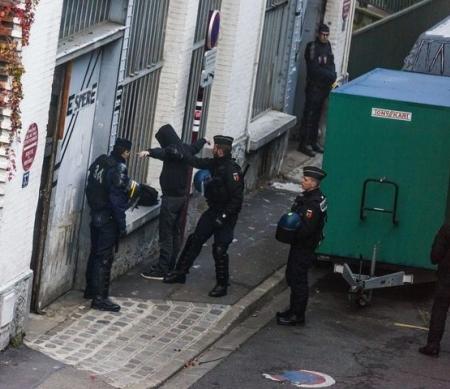 Politieagenten onderzoeken een man tijdens een raid in Le Pre Saint-Gervais, 27 november 2015 © .LAURENT EMMANUEL/AFP/Getty Images