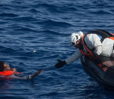 Een bemanningslid van het Migrant Offshore Aid Station (MOAS) rijkt de hand uit naar een man om hem aan boord van een reddingsboot te trekken, Mei 2018 © Chris McGrath/Getty Images