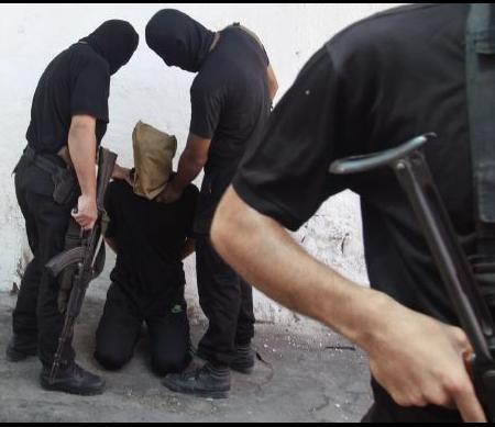 Militanten van Hamas pakken een van collaboratie verdachte Palestijn op - Foto: Reuters