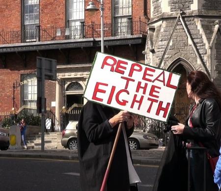 """Een vrouw houdt een bord met de boodschap""""Repeal the Eighth"""" klaar voor het protest in Dublin (27 september 2014)"""