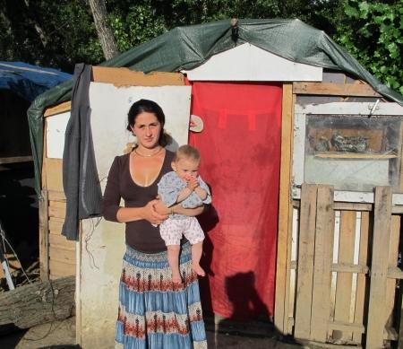 Roma familie voor hun huis in een kamp bij Lyon