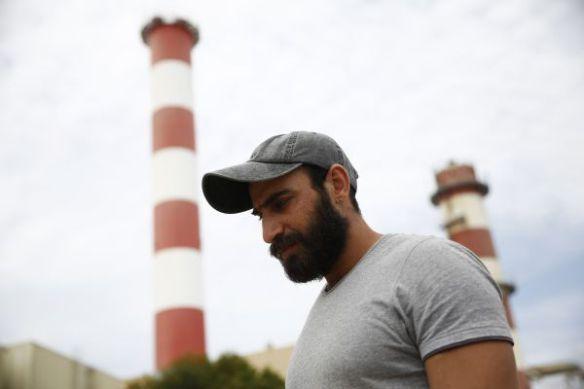 """Hani, een 31-jarige Syriër, kwam aan op Chios op 20 maart, de dag dat de EU-Turkijedeal van kracht ging. Sindsdien zit hij nog steeds vast. Hij slaapt naast andere families in het informele kamp in Dipethe. Zijn familie is nog in Syrië: """"Ik bel hen elke dag om te checken of ze nog leven."""" © Giorgos Moutafis"""