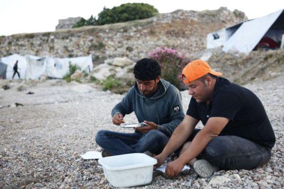 Twee mannen eten naast het Soudakamp in Chios. Lokale en internationale vrijwilligers zorgen voor hun maaltijden, maar hun middelen geraken uitgeput. Hun solidariteit staat in schril contrast met de inspanningen van de EU om vluchtelingen buiten te houden op een moment van grote nood © Giorgos Moutafis