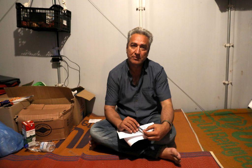 """Anwar (45) is een chirurg uit Hoss, Afghanistan. Samen met zijn vrouw en twee zonen vluchtte hij weg uit Kabul om veiligheidsredenen. Het gezin woont sinds eind  april  in een tent in Souda kamp en  hebben asiel aangevraagd. De twee jongens missen hun school. Anwar vertelt over de erbarmelijke omstandigheden in het kamp, de gevechten tussen groepen, de racistische aanvallen en de angst die de vrouwen in het kamp ervaren. """" 'S Avonds ga ik met mijn vrouw naar het toilet, omdat we ons hier niet veilig voelen ...."""" © Giorgos Moutafis/Amnesty International"""
